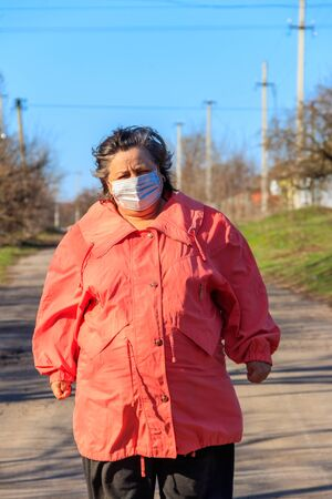Senior woman stands in a medical mask on her face, which protects against coronavirus and other viruses and diseases on a rural street. Coronavirus pandemic Stock Photo