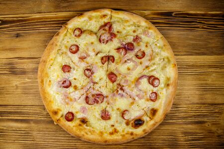 Delicious fresh pizza with sausage, red onion and cheese on a wooden table. Top view