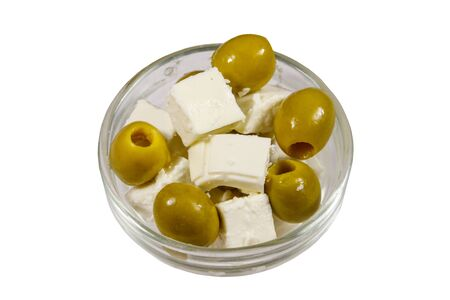 Feta cheese cubes with green olives in glass bowl isolated on white background