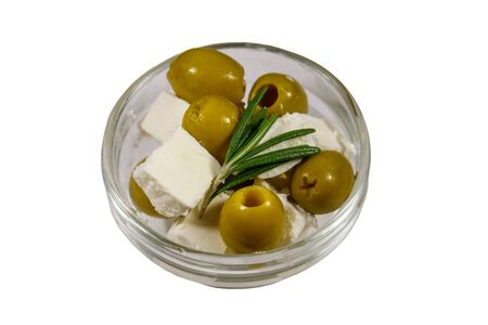 Feta cheese cubes with green olives and rosemary in glass bowl isolated on white background Banque d'images