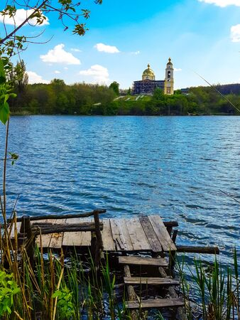 View on old orthodox church on a shore of the beautiful lake and small wooden pier with bench for fishing Фото со стока
