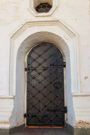 Close-up of the old black iron arched door