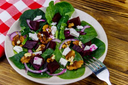 Tasty spinach salad with boiled beetroot, feta cheese, walnut and red onion on wooden table. Healthy vegetarian food