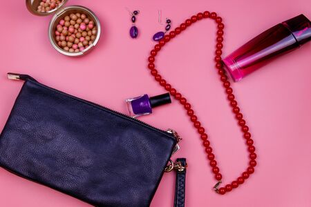 Clutch bag, red necklace, earrings, nail polish, rouge balls and bottle of perfume on pink background. Beauty and fashion concept. Flat lay, top view
