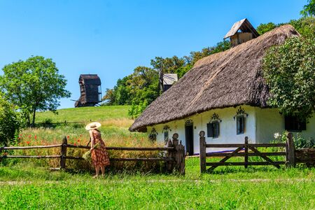 Young woman in straw hat collects flowers near ancient traditional ukrainian rural house