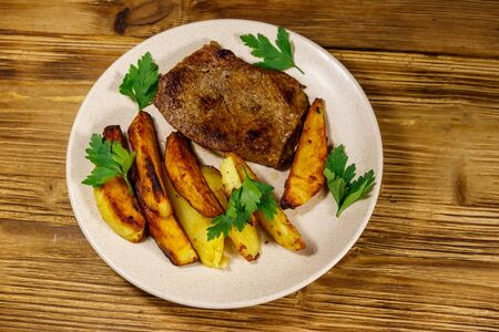 Fried beef steak with potato wedges on wooden table. Top view Zdjęcie Seryjne