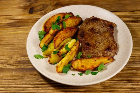 Fried beef steak with potato wedges on wooden table