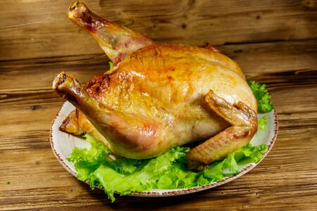Baked whole chicken on a wooden table