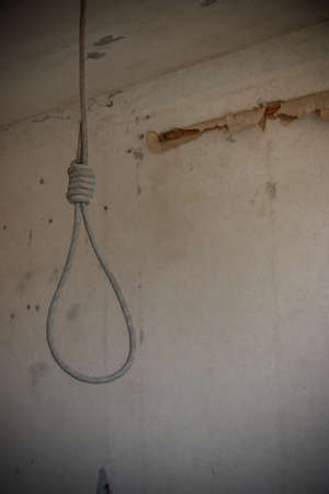 Deadly loop hanging from the ceiling in abandoned apartment. Concept of suicide, despair 스톡 콘텐츠