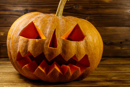 Spooky Halloween pumpkin jack-o-lantern on a wooden background Stock Photo