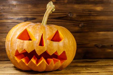Spooky Halloween pumpkin jack-o-lantern on a wooden background 免版税图像 - 151106680