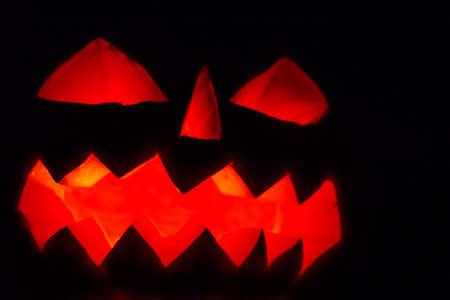 Spooky Halloween pumpkin jack-o-lantern with burning candles on dark background 免版税图像 - 151106964