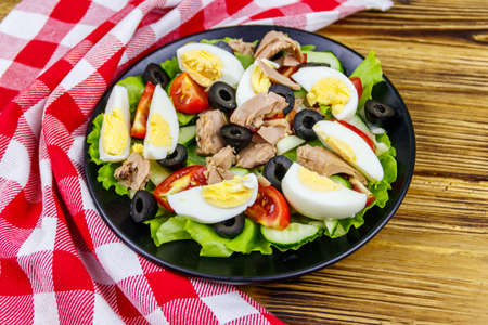 Tasty tuna salad with lettuce, black olives, eggs and fresh vegetables on wooden table