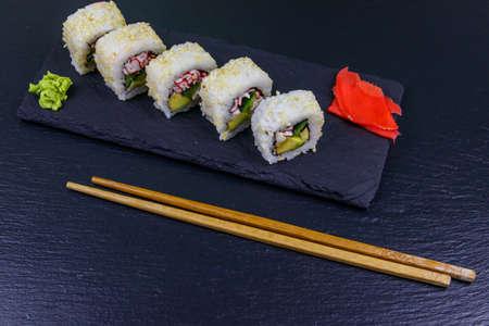 Uramaki sushi rolls with surimi on a black slate Standard-Bild