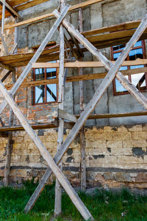 Reconstruction of old building with old wooden scaffolding
