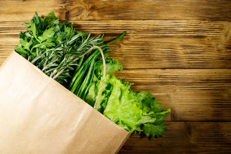 Paper bag with green onion, rosemary, lettuce leaves and parsley on wooden table. Top view. Healthy food and grocery shopping concept