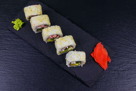 Uramaki sushi rolls with surimi on a black slate. Top view