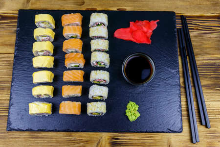 Set of sushi rolls on a black stone slate on wooden table. Top view