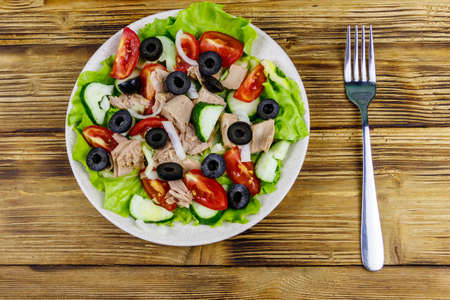 Tasty tuna salad with lettuce, black olives and fresh vegetables on wooden table. Top view