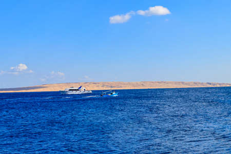 Old fishing boat and white luxury yacht sails in the Red sea, Egypt