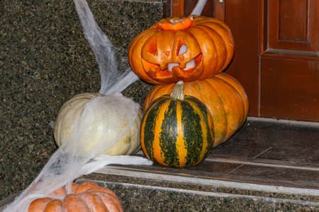 Spooky Halloween pumpkin jack-o-lanterns with spider web on the steps at a door. Decorations for Halloween holiday 写真素材