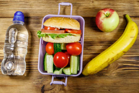 Bottle of water, apple, banana and lunch box with burgers and fresh vegetables on a wooden table. Top view 写真素材