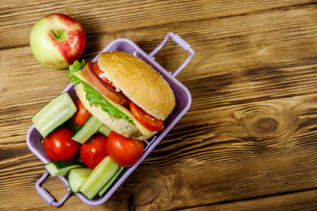 Apple and lunch box with burgers and fresh vegetables on a wooden table. Top view 写真素材