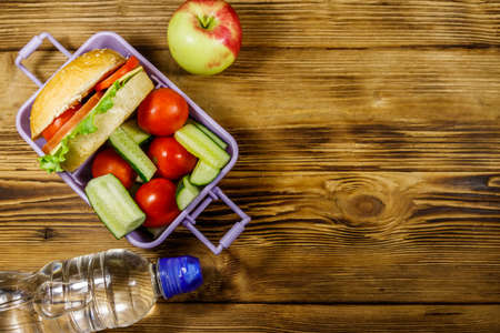 Bottle of water, apple and lunch box with burgers and fresh vegetables on a wooden table. Top view, copy space 写真素材
