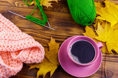 Cup of coffee, ball of yarn, knitting, knitted scarf and yellow maple leaves on wooden table. Autumn still life 写真素材 - 152454117