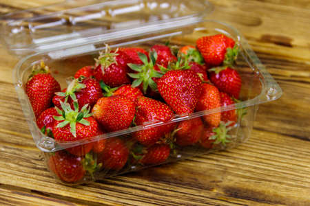 Fresh strawberry in plastic box on a wooden table