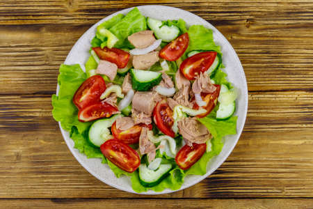 Tasty tuna salad with lettuce and fresh vegetables on wooden table. Top view