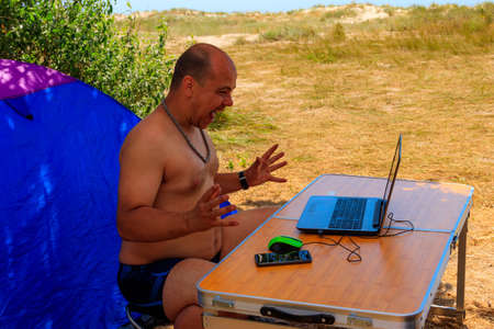 Man using his laptop sitting at a folding picnic table in a camping. Working while traveling. Freelance work. Work and travel concept