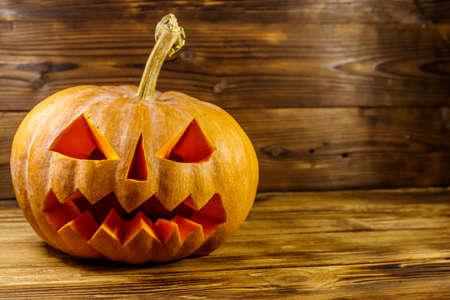 Spooky Halloween pumpkin jack-o-lantern on a wooden background