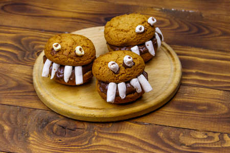 Halloween dessert: Toothed monsters made of oatmeal cookies, chocolate spread and marshmallows on a wooden table Фото со стока