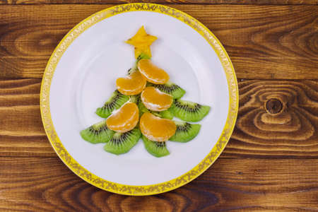 Christmas tree made of kiwi slices and mandarin lobules on wooden table. Top view. Creative idea for Christmas and New Year festive desserts. Funny food idea for kids