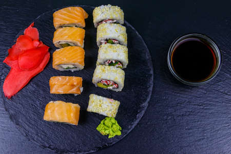 Set of sushi rolls on a black stone slate. Top view 写真素材