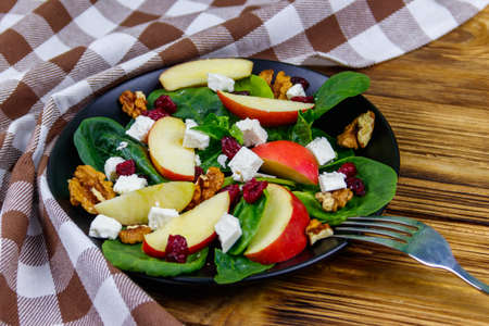 Autumn spinach salad with apple, feta cheese, walnut and dried cranberry on wooden table. Healthy vegetarian food 写真素材
