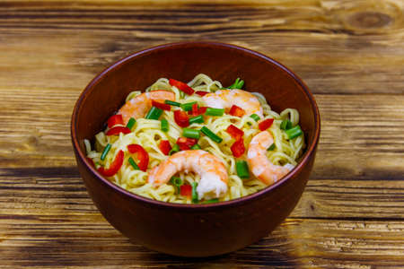 Bowl of instant Chinese noodles with shrimps, green onion and red hot chilli peppers on wooden table