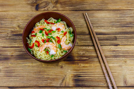 Bowl of instant Chinese noodles with shrimps, green onion and red hot chilli peppers on wooden table. Top view 写真素材