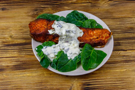 Grilled salmon fillet with spinach and tartare sauce on wooden table