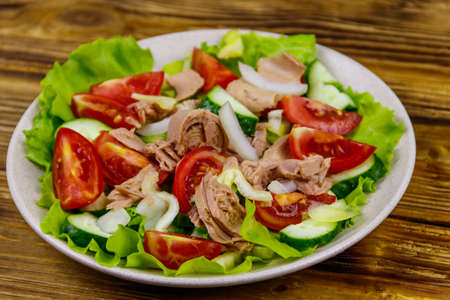 Tasty tuna salad with lettuce and fresh vegetables on wooden table