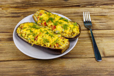 Baked stuffed eggplants on a wooden table. Healthy food and dieting concept