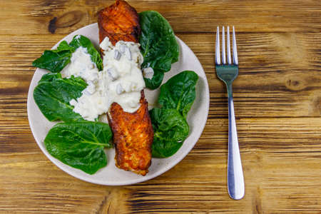 Grilled salmon fillet with spinach and tartare sauce on wooden table. Top view