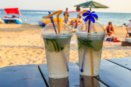 Two fresh mojito cocktails on a table on a background of tropical beach