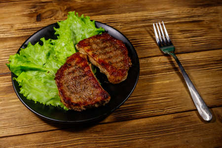 Grilled pork steaks with lettuce leaves on wooden table 写真素材