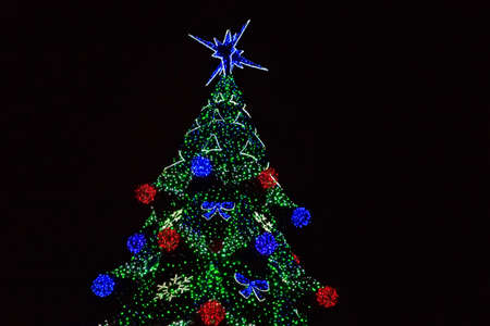 Decorated Christmas tree with multi-colored lights at night 写真素材