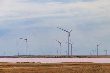 Wind turbines on a shore of the pink salty Syvash lake in Kherson region, Ukraine. Renewable energy