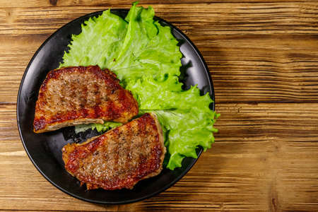 Grilled pork steaks with lettuce leaves on wooden table. Top view