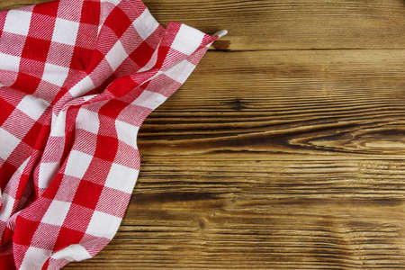 Red folded checkered napkin on rustic wooden kitchen table. Top view, copy space