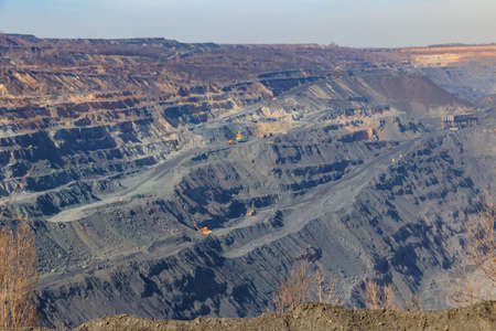 Huge iron ore quarry with working dump trucks and excavators